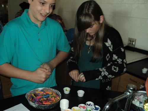 Students preparing candle wicks from crayons