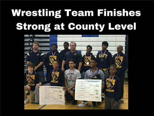 Image of wrestling team with awards and holding the bracket
